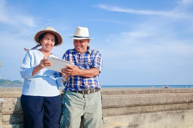 Asiatische paare, senioren machen gemeinsam aktivitäten, kommen ans meer und benutzen smart tablets.