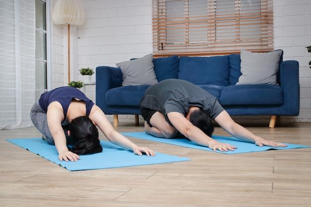 Asiatische paare trainieren zusammen zu hause im wohnzimmer. für gesundheit und soziale distanz sorgen während covid 19
