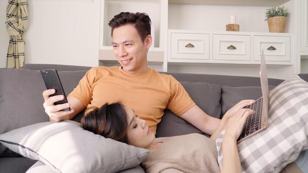 Asiatische paare unter verwendung des smartphone und des laptops, die zu hause social media im wohnzimmer überprüfen