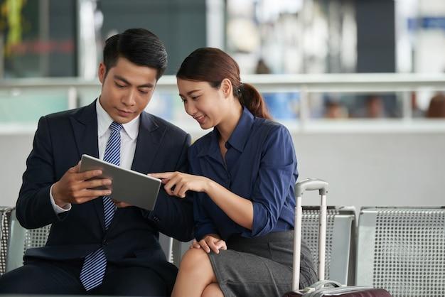 Asiatische paare unter verwendung des tablets im flughafen