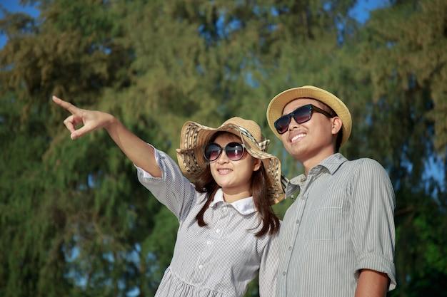 Asiatische paare zeigen ihre finger auf den strand zur sommerzeit
