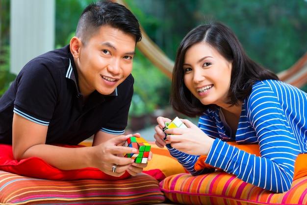 Asiatische paare zu hause, die mit magischem würfel spielen