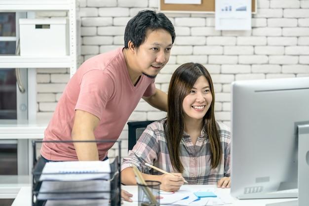 Asiatische paarkollegen, die im modernen büro mit technologiecomputern zusammenarbeiten