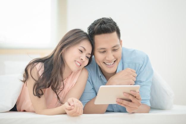 Asiatische paarliebhaber genießen, on-line-film auf intelligenter tablette auf feiertagsferien im schlafzimmer aufzupassen.