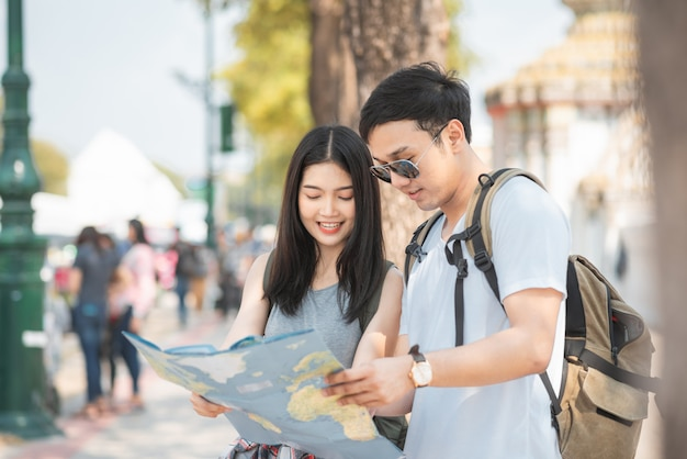 Asiatische paarrichtung des reisenden auf standortkarte in bangkok, thailand