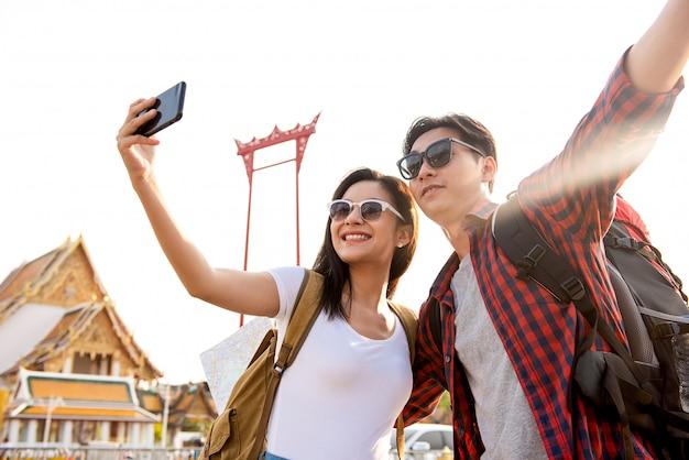Asiatische paartouristen, die selfie beim reisen in bangkok thailand nehmen