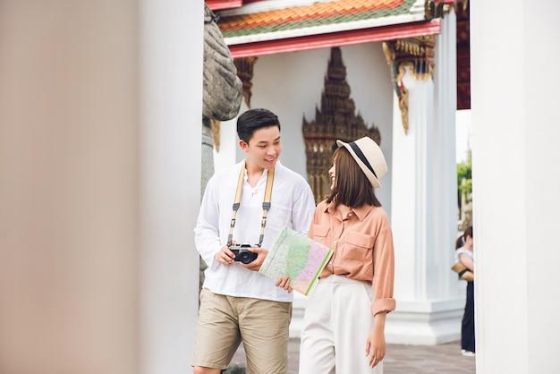 Asiatische paartouristen, die thailändischen tempel in bangkok thailand an den sommerferien besuchen
