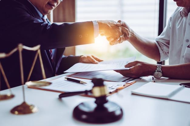 Asiatische partnerrechtsanwälte des mittelalters, die hände rütteln, nachdem eine abgeschlossene vertragsvereinbarung besprochen worden ist.