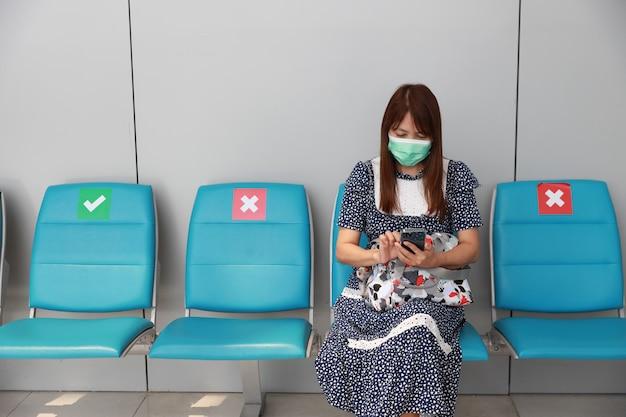 Asiatische passagierin, die während des ausbruchs von covid19 mit smartphone und im flughafenterminal sitzt mit schutzmaske.