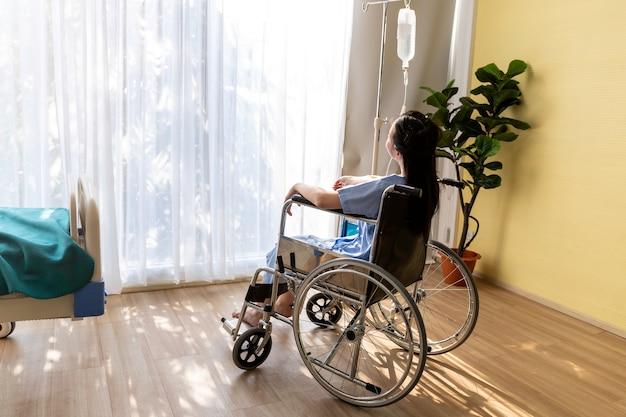 Asiatische patientin, die im rollstuhl am krankenzimmer sitzt.