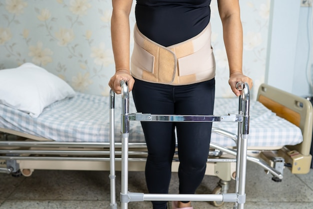 Asiatische patientin, die rückenschmerzunterstützungsgürtel mit gehhilfe trägt.