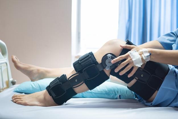 Asiatische patientin mit bandagekompressions-knieorthese-stützverletzung auf dem bett im pflegekrankenhaus. gesundheitsfürsorge und medizinische unterstützung.