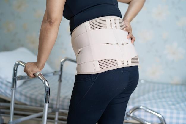 Asiatische patientin mit rückenschmerz-stützgürtel für die orthopädische lendenwirbelsäule mit gehhilfe