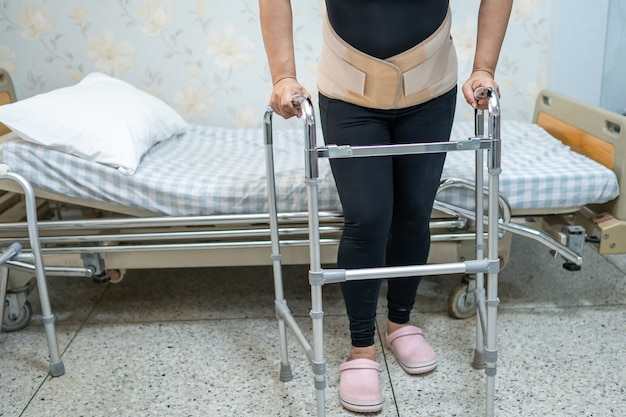Asiatische patientin mit rückenschmerzen-unterstützungsgurt für orthopädische lendenwirbelsäule mit gehhilfe.