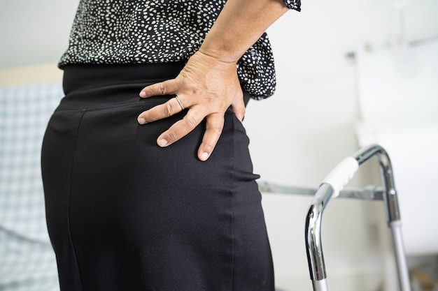 Asiatische patientin schmerzt ihre orthopädische lendenwirbelsäule am handgelenk mit gehhilfe.
