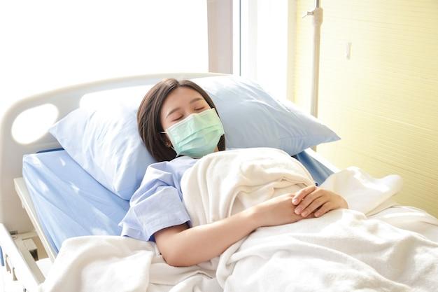 Asiatische patientinnen tragen eine blaue maske und liegen in einem krankenhausbett