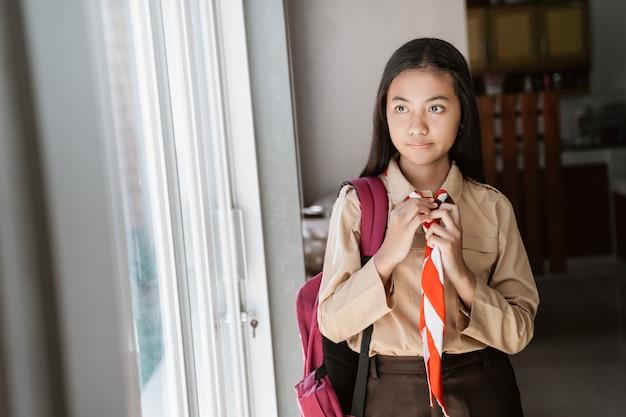 Asiatische pfadfinderin, die sich vor dem schulbesuch vorbereitet