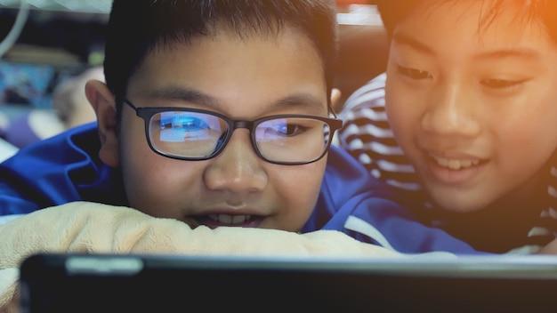 Asiatische preteens, die auf tablet-computer aufpassen, lächeln gesicht.