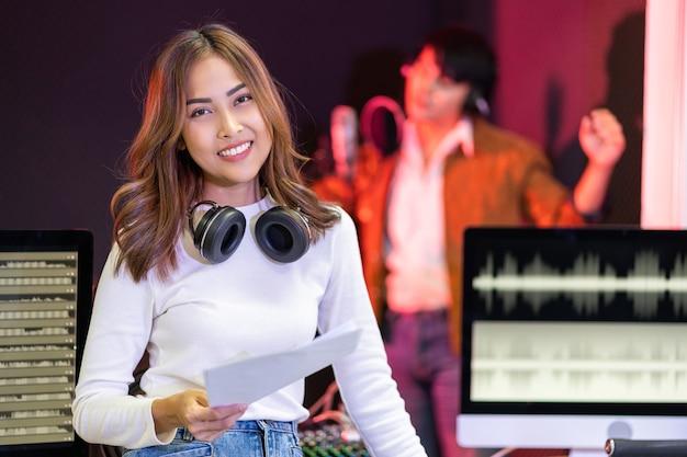 Asiatische produzentin im weißen hemd, das durch tonmischkonsole steht glückliche komponistin des musikkomponisten