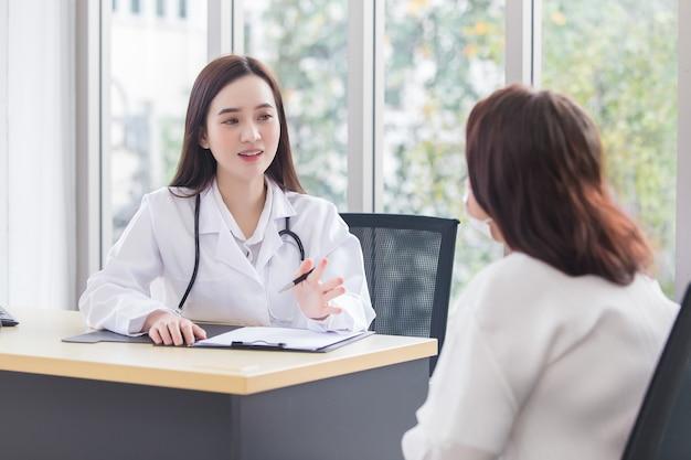 Asiatische professionelle ärztin, die einen medizinischen mantel trägt, spricht mit einer patientin
