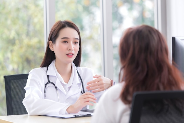 Asiatische professionelle ärztin schlägt ihren älteren patienten bei der untersuchung eine gesundheitslösung vor