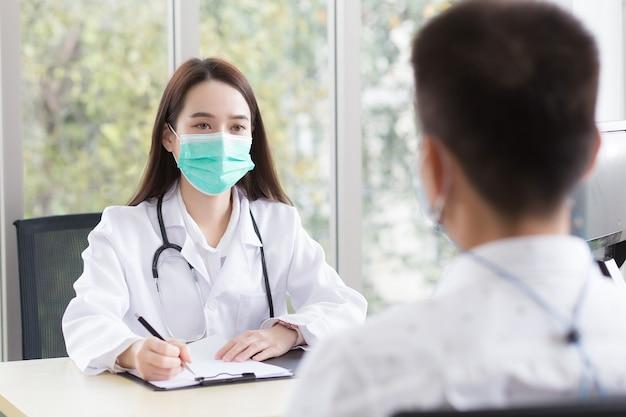 Asiatische professionelle ärztin trägt bei untersuchungen und gesprächen einen medizinischen mantel und eine gesichtsmaske