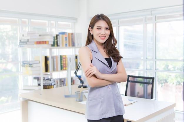 Asiatische professionelle geschäftsfrau, die ein graues hemd trägt, steht für selbstvertrauen und smart