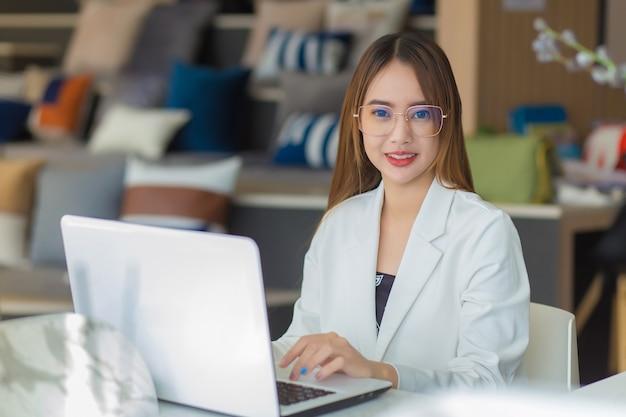 Asiatische professionelle geschäftsfrau mit brille arbeitet im coworking space mit laptop-papierkram
