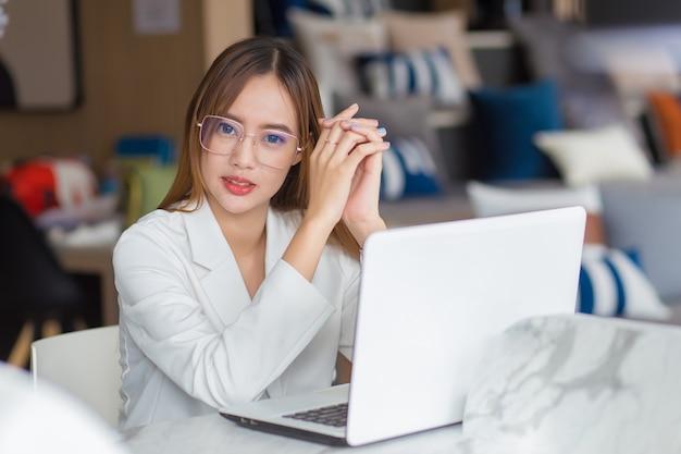 Asiatische professionelle geschäftsfrau mit brille arbeitet, während sie in die kamera schaut und im co-working-space mit laptop sitzt, papierkram (geschäftsfrauenkonzept).