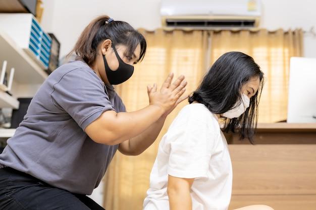 Asiatische quarantänefrau massieren zu hause mit gesichtsmaske