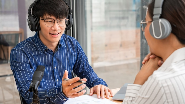 Asiatische radiomoderatoren gestikulieren auf ein mikrofon, während sie einen mann in einem studio interviewen, während sie gemeinsam einen podcast für eine online-show im studio aufnehmen.