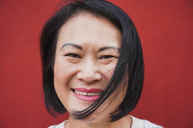 Asiatische reife frau, die vor kamera lächelt - porträt der älteren frau mit rotem hintergrund - freudiger älterer lebensstil und reales personenkonzept - fokus auf gesicht