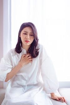Asiatische reife frau mit herzinfarktproblemen, die sich unwohl fühlen in den extremitäten brustschmerzen erleben