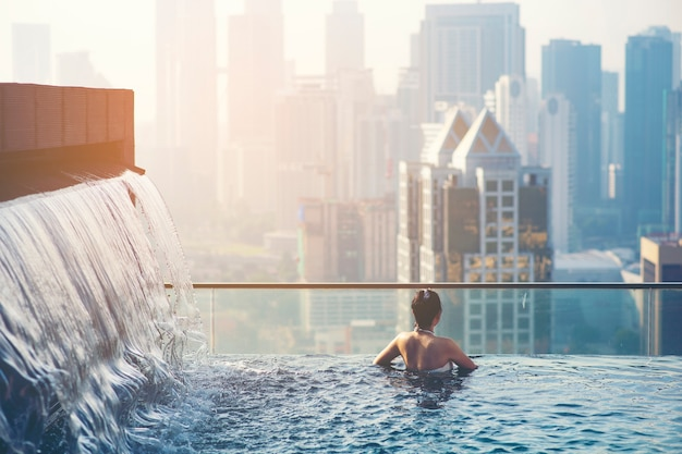 Asiatische reise. junge frau, die die stadtansicht vom dachspitzenswimmingpool genießt.