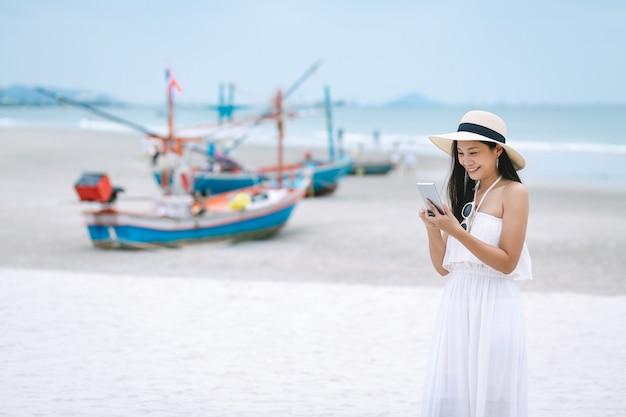 Asiatische reisende frau, die handy am strand verwendet