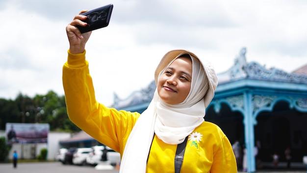 Asiatische reisende frau, die selfies am keraton solo nimmt
