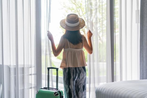 Asiatische reisende frau, die strohhut trägt