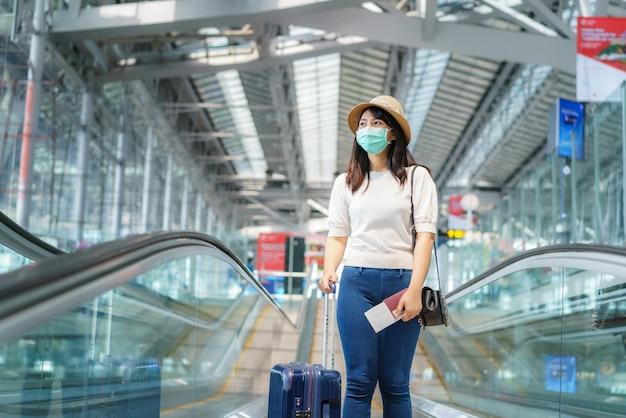 Asiatische reisende frau mit gepäck, das gesichtsmaske trägt, die außerhalb des terminals im flughafen schaut