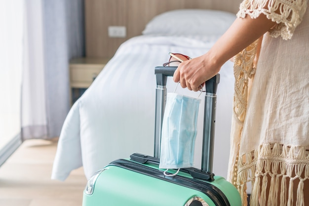 Asiatische reisende frau mit grünem gepäck und chirurgischer maske im hotelzimmer nach dem einchecken. reisen, gesundheitswesen und neues normales konzept.