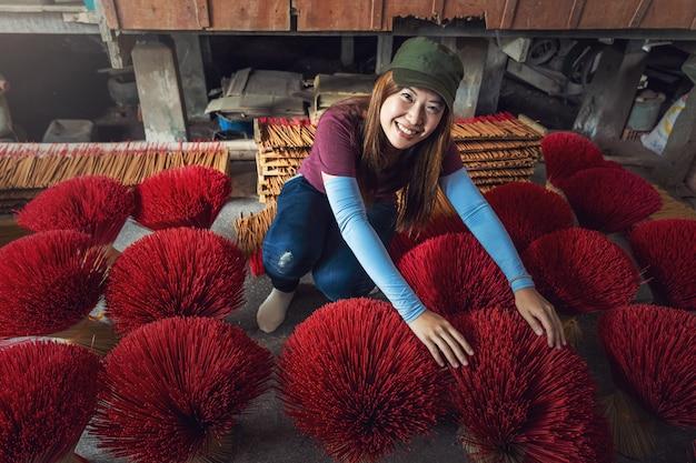 Asiatische reisendfrau, die den traditionellen vietnam-roten unsinn im alten traditionellen haus an langem xuyen, an einem giang provinz-, vietnam-, traditionellem- und kulturkonzept macht