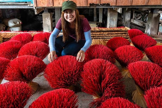 Asiatische reisendfrau, die den traditionellen vietnam-roten unsinn im alten traditionellen haus bei langem xuyen, eine giang provinz, vietnam macht