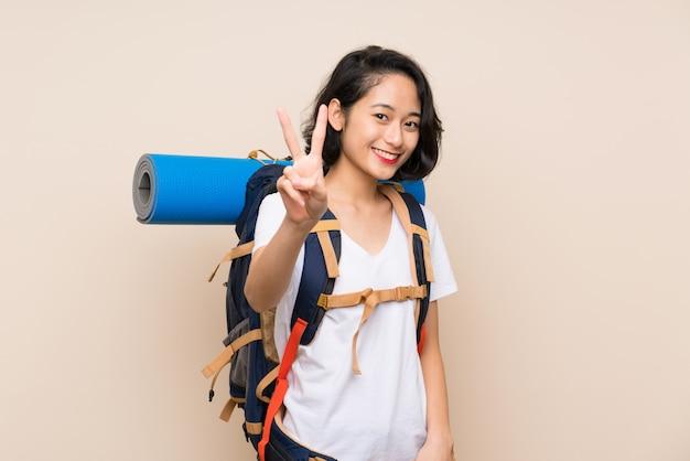 Asiatische reisendfrau, die siegeszeichen lächelt und zeigt