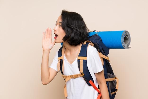 Asiatische reisendfrau über der lokalisierten wand, die mit dem breiten mund schreit, öffnen sich
