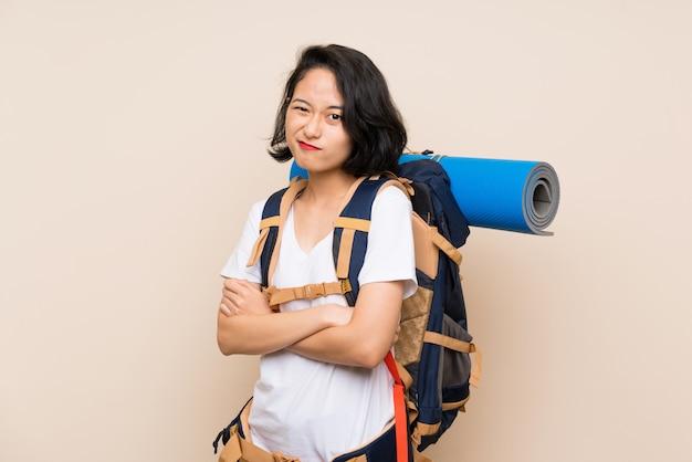 Asiatische reisendfrau über lokalisierter herstellung zweifelt geste beim anheben der schultern
