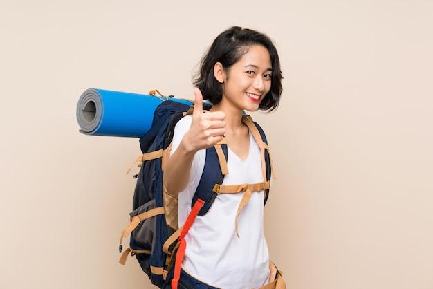 Asiatische reisendfrau über lokalisierter wand mit den daumen oben, weil etwas gutes geschehen ist