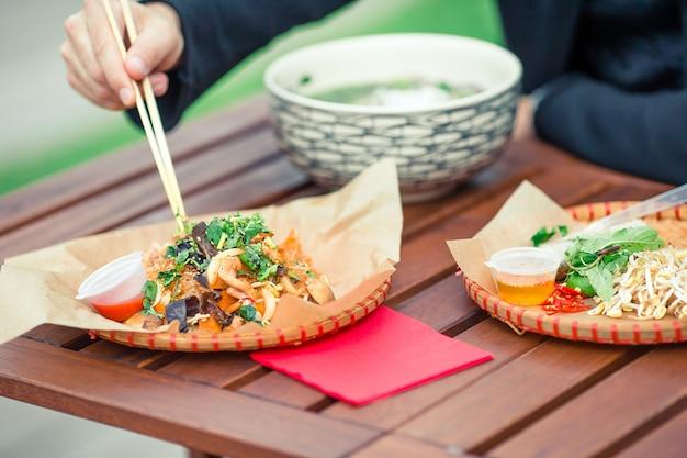 Asiatische reisnudeln mit gemüse und sause nahaufnahme auf dem tisch