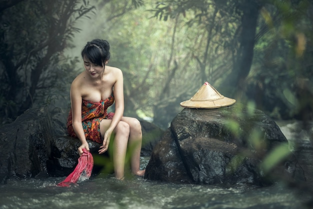 Asiatische reizvolle frau, die in den strömen sich wäscht