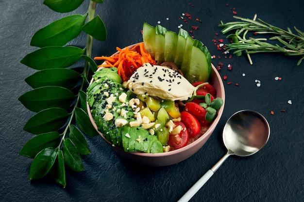 Asiatische sackschale mit frischkäse, avocado, kirschtomaten, gurken- und shiitake-pilzen auf einem schwarzen tisch. leckeres und diät-essen. draufsicht und fla lag mit kopierraum