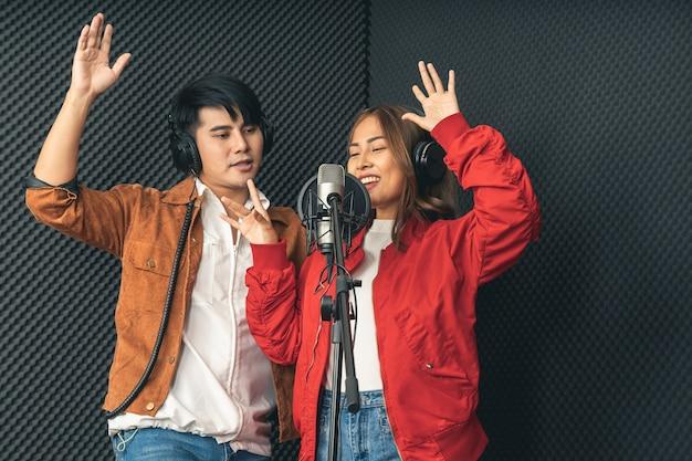 Asiatische sängerpaare in einem aufnahmestudio mit einem studiomikrofon mit leidenschaft im musikaufnahmestudio