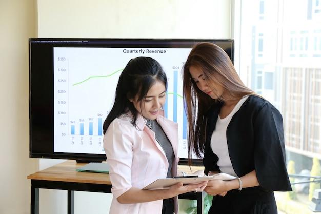 Asiatische schicke intelligente frauenhandarbeit der reizend schönen sonnenbräunehaut am laptoptelefon und schreiben stift auf notizbuchmolkerei auf holztisch im büro. präsentieren sie ihr produkt mit frau gute arbeitsleistung.